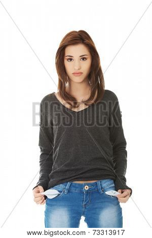 Sad young woman taking out empty pockets