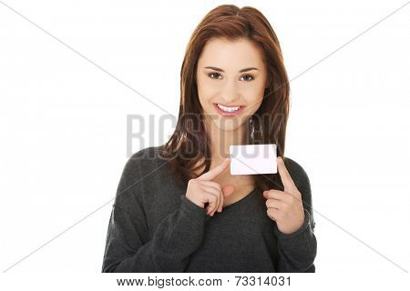 Casual happy woman showing business card