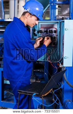industrial engineer repairing computerized machine with laptop computer