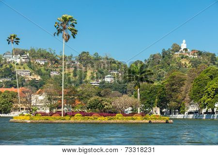 KANDY, SRI LANKA - FEBRUARY 26, 2014: View on Kandy lake and big Buddha on top of the hill. Kandy is home of The Temple of the Tooth Relic, one of the most sacred Buddhist places of worship.