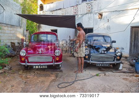 UNAWATUNA, SRI LANKA - MARCH 6, 2014: Local man washing two Morris Minor cars in the yard with water hose. There are estimated to be as many as 4,000 Minors still on the road in Sri Lanka.