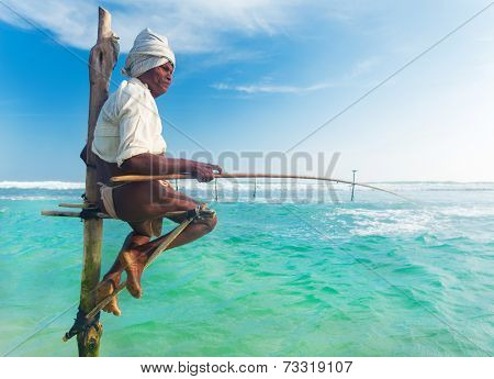 UNAWATUNA, SRI LANKA - MARCH 9, 2014: Elderly stilt fisherman at Hikkaduwa Beach. Most real stilt fishermen have been long gone. Today it's mainly young boys posing as stilt fishermen for tourists.
