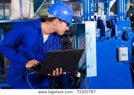 industrial technician checking distribution box with laptop in factory