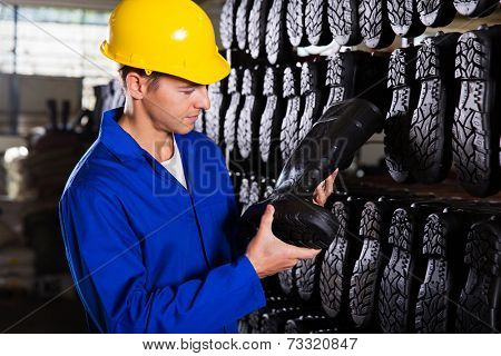 factory worker looking at gumboots in a storeroom