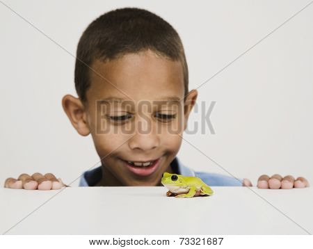 African boy looking at frog