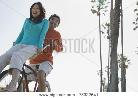 Asian man riding bicycle with girlfriend on handlebars