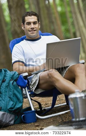 Hispanic man typing on laptop
