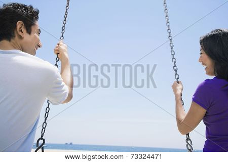Asian couple swinging on swings