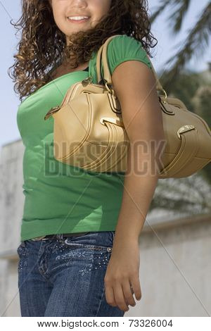 Hispanic teenaged girl carrying shoulder bag