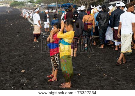 BALI, INDONESIA - SEPTEMBER 19, 2014: Two young girls pray at a the Nyaben 12th day ceremony, a day to throw the cremated ashes into the sea, a sign of releasing the soul for reincarnation.