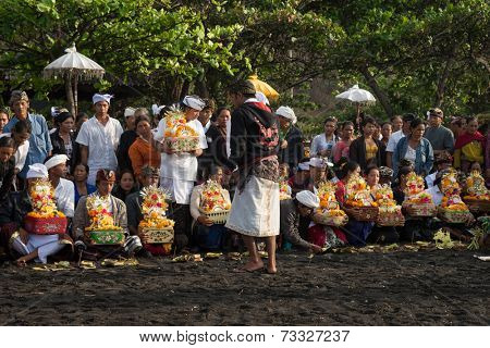 BALI, INDONESIA - SEPTEMBER 19, 2014: Families gather at the beach bringing offerings for the Nyaben ceremony, to throw the cremated ashes into the sea, a sign of releasing the soul for reincarnation.