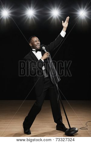 African American man in tuxedo singing into microphone onstage