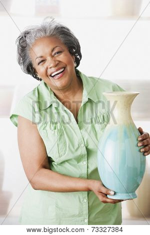 African woman holding ceramic vase