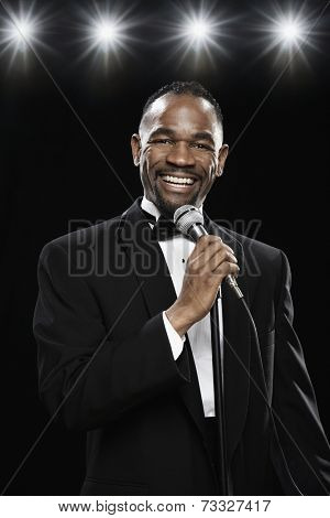 African American man in tuxedo holding microphone