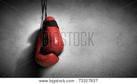 Pair of red boxing gloves hanging on wall