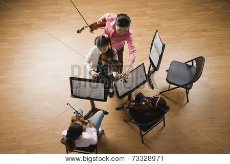 Asian female music teacher helping student play violin