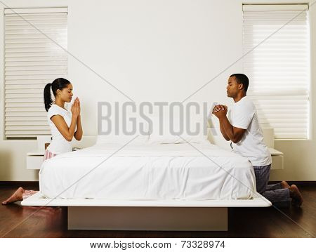 African couple praying at bedside