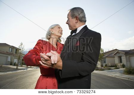 Well dressed senior couple dancing in suburban street
