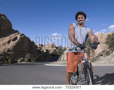 African man standing on mountain bike