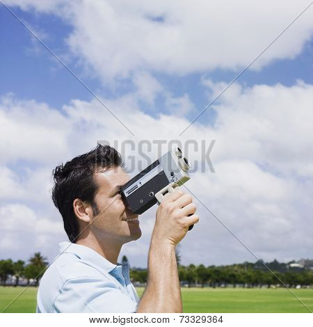 Mixed Race man looking through old fashioned film camera