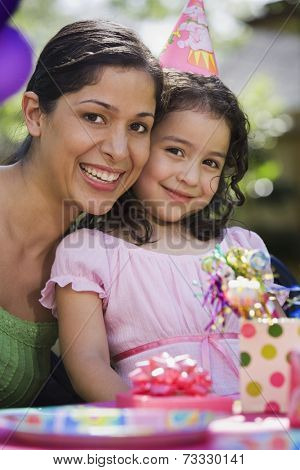 Hispanic mother and daughter at outdoor birthday party