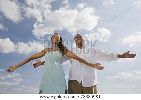African couple with arms outstretched