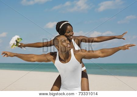 African bride and groom with arms outstretched at beach