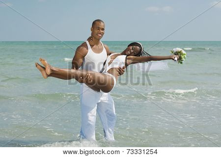 African groom carrying bride at beach