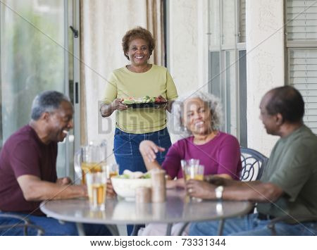 Senior African couples eating on patio