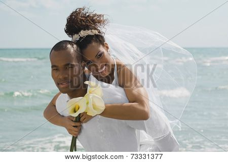 Multi-ethnic bride and groom hugging at beach
