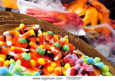 a pile of different Halloween candies with scary ornaments in the background, such as an amputated hand, cobwebs and pumpkins