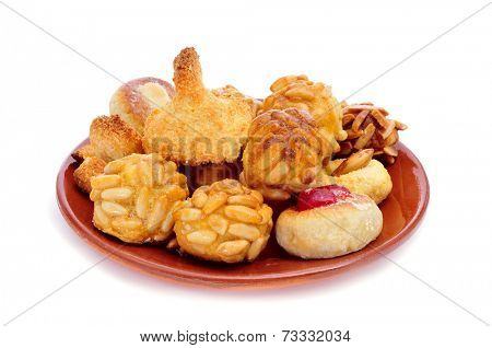 an earthenware plate with panellets, typical pastries of Catalonia, Spain, eaten in All Saints Day, on a white background