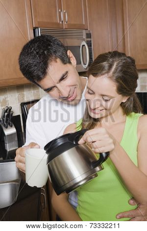 Hispanic woman pouring coffee for husband