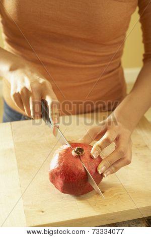 Asian woman cutting pomegranate