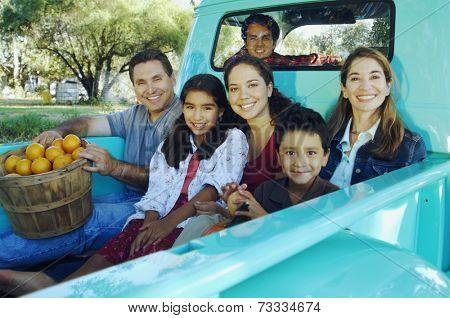 Multi-ethnic family in back of truck