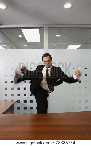 Businessman kicking over desk
