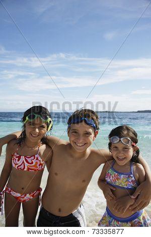 Hispanic siblings hugging at beach