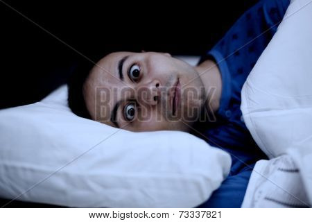 Portrait of an insomniac man trying to sleep in his bed