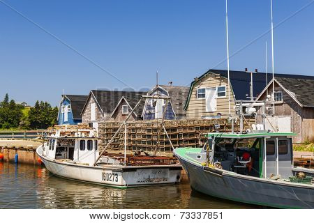 CAVENDISH, PRINCE EDWARD ISLAND, CANADA - JULY 15 2013: Fishing boats docked near lobster traps shown on July 15, 2013 in Cavendish, Prince Edward Island, Canada