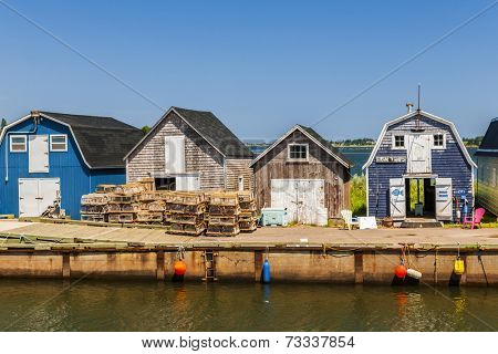 CAVENDISH, PRINCE EDWARD ISLAND, CANADA - JULY 15 2013: Fishing pier with buildings and lobster traps shown on July 15, 2013 in Cavendish, Prince Edward Island, Canada