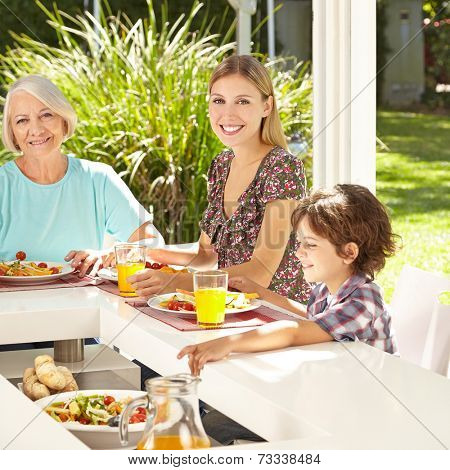Child eating lunch salad with mother and grandmother in summer