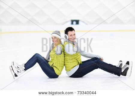A picture of a happy couple sitting on the skating rink
