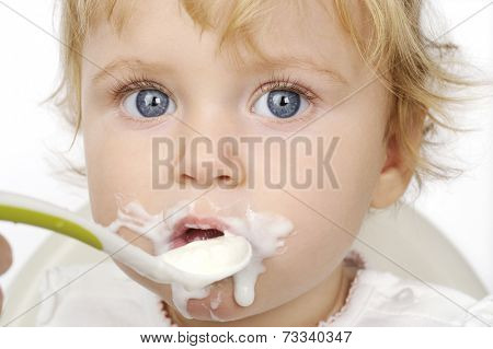 The baby girl eating with spoon with white background