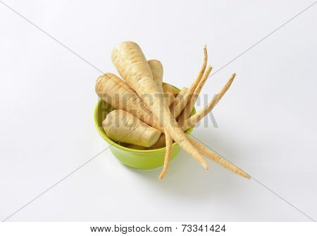 bowl of parsley roots on white background