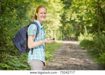 Woman Navigating An Outdoor Trip In A Forest