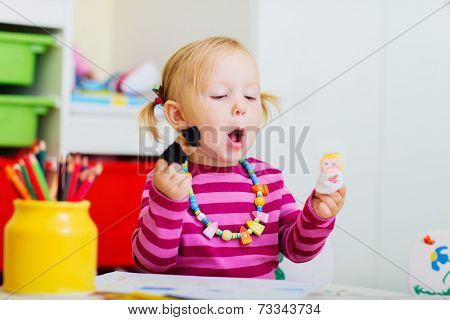 Adorable toddler girl playing with finger puppets at home or daycare