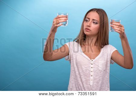 Portrait of a pretty girl holding two glasses with clean water i