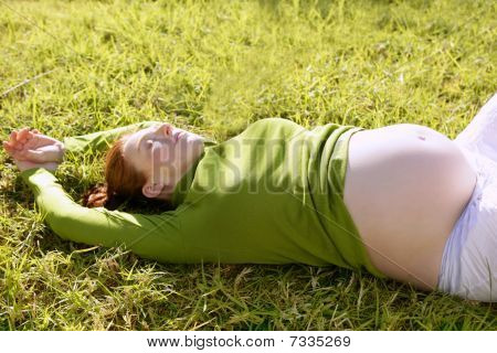 Pregnant Woman Redhead Laying On Grass