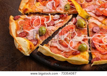 Pizza with tomato, salami, peppeeoni, olives and yellow hot pepper