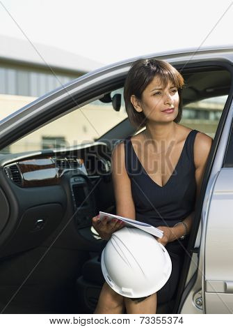 Indian woman holding hard hat in car